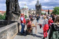 Prague tjeck - Juli 30, 2007 - en rolig man med ett positiv på Charles Bridge över den Vltava floden royaltyfri fotografi