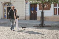 Prague Tjeckien - April 19, 2011: Ett par går i fyrkanten med hennes lilla hund De poserar för ett foto arkivbild