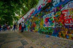 Prague Tjeckien - 13 Augusti, 2015: Den berömda John Lennon väggen som fylldes upp med förälskelse, inspirerade grafitti i stadsm Arkivbild