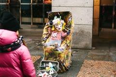 Prague Tjeckien, December 24, 2016 - en rolig clown en vuxen människa förställas som ett barn i en sittvagn underhållning Arkivfoton