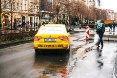 Prague Tjeckien - December 24, 2016 - gul taxi på framsidorna av staden Fotografering för Bildbyråer