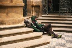 Prague Tjeckien December 24, 2016 - hemlöst hungrigt sammanträde för fattig man på trottoaren i centret olyckligt Arkivbild