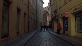 PRAGUE TJECKIEN - DECEMBER 3, 2016 skottet för steadicam 4K av en smal kullersten stenlade gatan och det lilla utomhus- kafét lager videofilmer