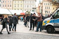 Prague Tjeckien - December 25, 2016: Tjeckiska poliser på en juldag hjälper turisten - visa det önskade stället Arkivfoto