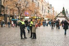 Prague Tjeckien - December 25, 2016: Tjeckiska poliser på en juldag hjälper turisten - visa det önskade stället Arkivfoton