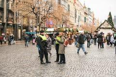 Prague Tjeckien - December 25, 2016: Tjeckiska poliser på en juldag hjälper turisten - visa det önskade stället Royaltyfria Bilder