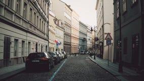 PRAGUE TJECKIEN - DECEMBER 3, 2016 videoen för steadicam 4K av en smal kullersten stenlade gatan med parkerade bilar gammalt lager videofilmer