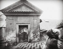 PRAGUE TJECKIEN: flickan upp trappan som förbigår de gamla gistna låga husen Väggarna faller ifrån varandra, den klottrade dörren Royaltyfri Foto