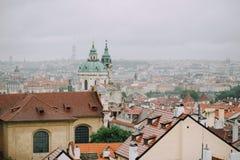Prague Tjeckien - Maj 2014 Sikt av staden i dimman och de röda taken och kyrkan av St Nicholas fotografering för bildbyråer