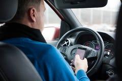 Prague Tjeckien - 21 01 1018: Man som använder den smarta telefonen i bil under körning Arkivfoto
