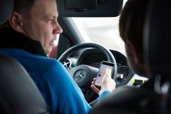 Prague Tjeckien - 21 01 1018: Man som använder den smarta telefonen i bil under körning Arkivbild
