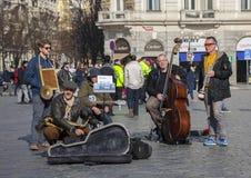 Prague Tjeckien - mars 13, 2017: Kvartett av musiker som spelar musikinstrument för turister på gatan i Prague royaltyfri fotografi