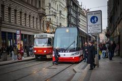 PRAGUE TJECKIEN - MARS 5, 2016: Tappningutfärdspårvagnen nummer 14 och den moderna spårvagnen nummer 9 ståtar är går på gammal st Royaltyfria Foton