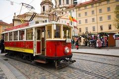 PRAGUE TJECKIEN - 9 12 2017: Retro spårvagn på den Prague gatan och jul som är ganska på bakgrund Royaltyfri Fotografi