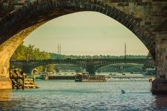 Prague Tjeckien - September, 17, 2019: Turister som går trought Charles Bridge, sikt från Vltava flodnivå arkivfoton