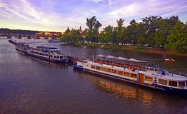 Prague, touristic boats at dusk moored on Moldau river Royalty Free Stock Images