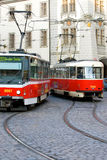 Prague Trolley Cars. Two trolley cars pass each other on the busy streets of Prague Stock Photo