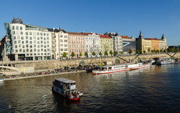 Prague waterfront and tour boats. Tourboats on the Vltava river in Prague and New Town buildings Fred and Ginger Dancing House Royalty Free Stock Photos