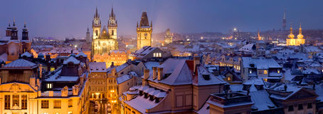 Prague at winter time. Panoramic photo of Prague  at winter time with snow on the roofs and night illumination of towers of Sv. Tyn, and city hall Royalty Free Stock Images