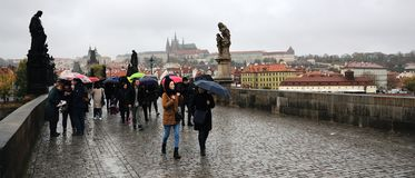 Praha, republika czech - Październik 28, 2018: ludzie z umrella na Karluv najwięcej Charles mostu w deszczowym dniu stulecie znaj fotografia stock
