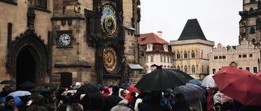 Praha Tjeckien - Oktober 28, 2018: Orloj astronomisk klocka på Staromestske namestifyrkant med folk under paraplyer in arkivfoto