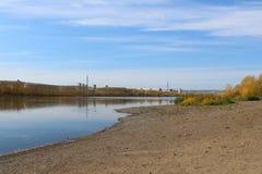 Praia abandonada arenosa urbana no outono: céu brilhante azul e água azul imagens de stock