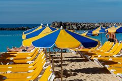 Praia aglomerada com os guarda-sóis e as cadeiras que esperam os turistas, serviço pago em praias fotografia de stock royalty free