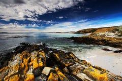 Praia amarela da rocha e da areia no nascer do sol Custe com obscuridade - onda azul e nuvens brancas no céu azul Custo rochoso n foto de stock