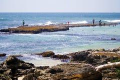 Praia bonita com água azul e as pedras escuras imagem de stock royalty free
