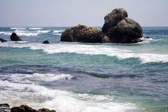 Praia bonita com água azul e as pedras escuras imagem de stock