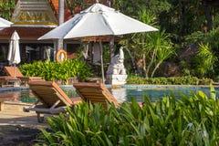 Praia bonita com piscina, palmeiras, daybeds e guarda-chuva em um jardim tropical perto do mar fotos de stock