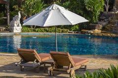 Praia bonita com piscina, palmeiras, daybeds e guarda-chuva em um jardim tropical perto do mar imagens de stock