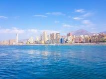 Praia bonita de Levante em Benidorm, Espanha Imagem tomada do mar, com a skyline dos arranha-c?us e um barco do primeiro motriz fotos de stock