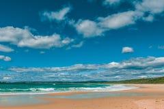 A praia bonita do oceano no dia ensolarado brilhante com as nuvens macias brancas ajardina Fotos de Stock