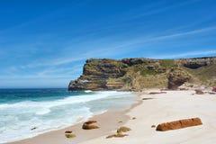 Praia branca com as rochas vermelhas ao lado das montanhas enevoadas Fotografia de Stock