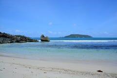 Praia branca da areia, rochas irregulares, e céu azul claro Foto de Stock