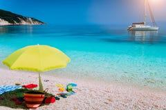 Praia branca idílico com o guarda-chuva no dia de verão preguiçoso Barco de navigação na âncora na água do mar azul claro calma foto de stock
