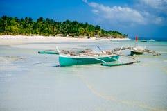 Praia branca tropical da areia com palmeiras verdes e os barcos de pesca estacionados na areia Paraíso exótico da ilha Fotografia de Stock