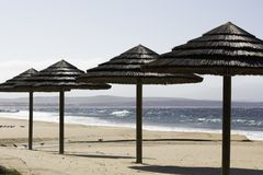 Praia cobrida com sapê Palapas do telhado e vista para o mar imagens de stock