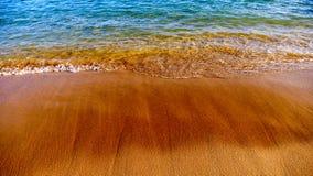 Praia com areia escura e água azul imagem de stock royalty free