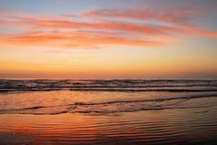 Praia com cores do nascer do sol fotografia de stock