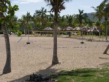 Praia com corte de voleibol e Tiki Shelters e palmeiras Imagem de Stock