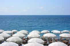 Praia com guarda-chuvas brancos Fotografia de Stock