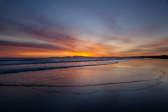 Praia com o céu alaranjado de Sun das ondas das nuvens Fotografia de Stock Royalty Free