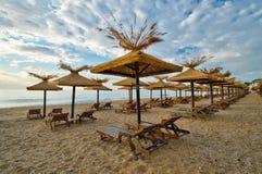 Praia com pára-sóis de madeira Imagens de Stock Royalty Free