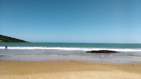 Praia com pedra e banhista Fotografia Stock