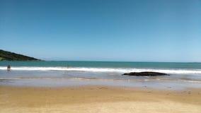 Praia com pedra e banhista Stock Photography