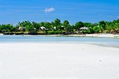 Praia coral branca bonita da areia com palmas e casas de campo, oceano do azul de turquesa Foto de Stock Royalty Free