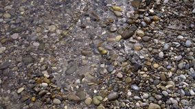 A praia da água da onda do banco apedreja a areia video estoque