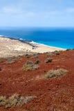 Praia da areia sob um vulcão vermelho imagens de stock royalty free
